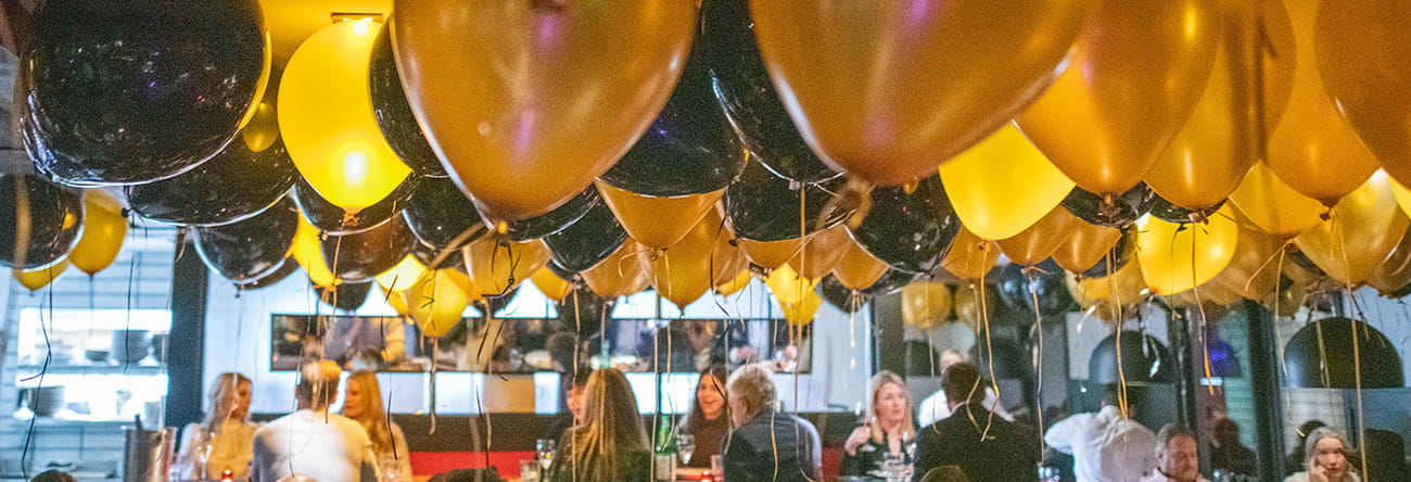 Balloons hover over diners at Ajax Tavern restaurant at The Little Nell for New Year's Eve Dinner.