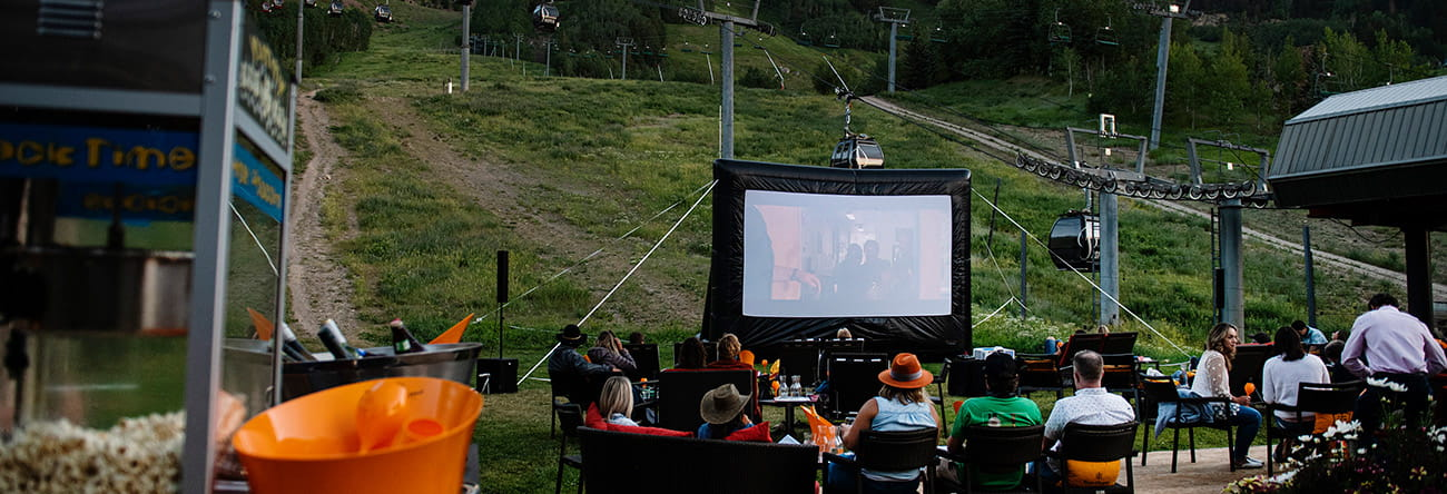 Guests enjoy dinner and a movie on Ajax Tavern's patio at the base of Aspen Mountain.