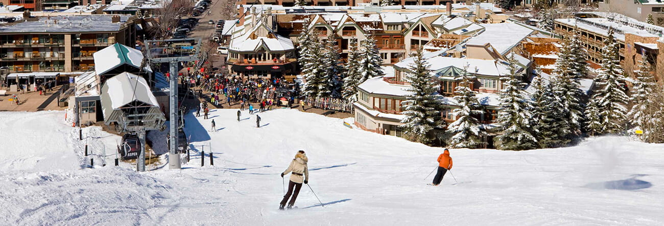 Guests skiing towards The Little Nell, Aspen's only ski-in/ski-out hotel.