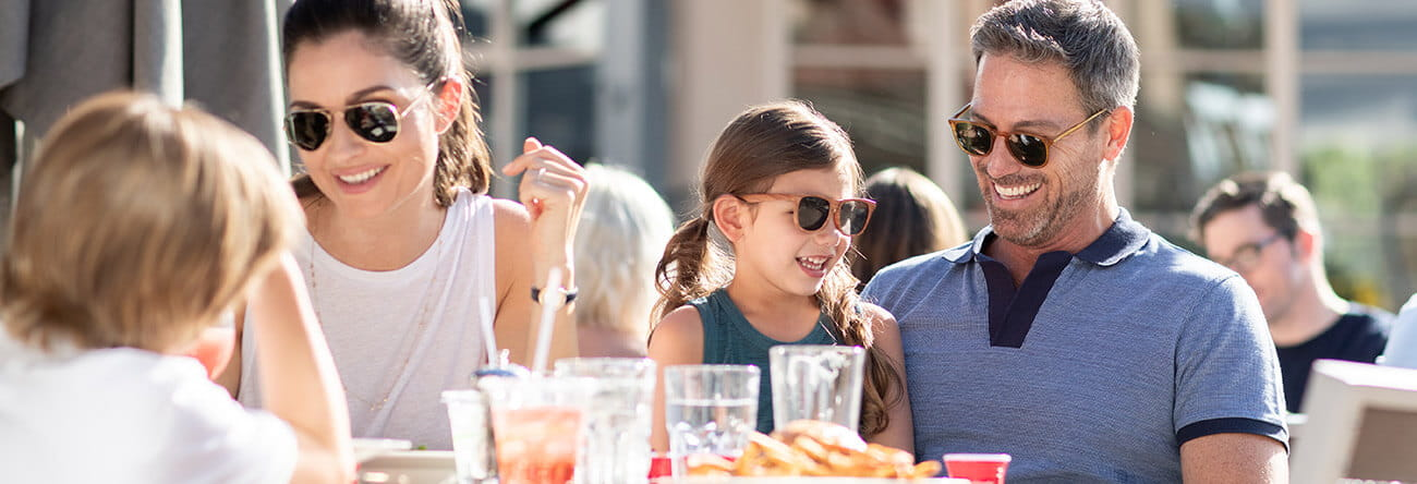 A family enjoys lunch on Ajax Tavern's sun-soaked patio at the base of Aspen Mountain.