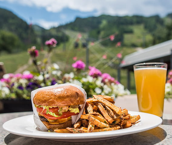 Ajax Tavern's popular wagyu double cheeseburger and fries sit on a table on the patio next to a draft beer.