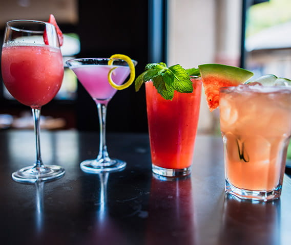 Four of Ajax Tavern's colorful cocktails, featuring the popular frose, sit on a table in the bar area.