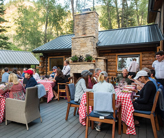 A group of people eating dinner on the patio at Mad Dog Ranch, where guests enjoy an al fresco dinner following a bike ride from the hotel.