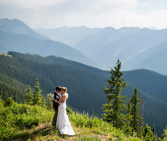 A couple stands atop Aspen Mountain before their wedding ceremony, surrounded by lush green grass and stunning mountains.