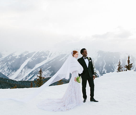 A couple stands on top of Aspen Mountain before their wedding ceremony, surrounded by snow-capped peaks.