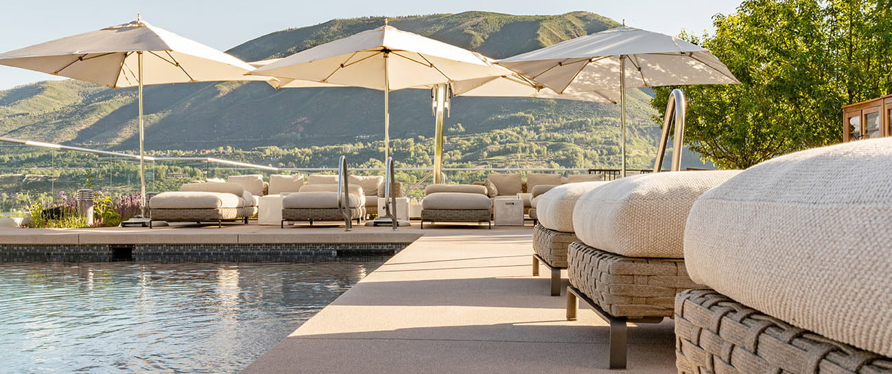 The rooftop pool at the Residences at The Little Nell offers plush patio furniture for guests to relax and enjoy sweeping mountain views.