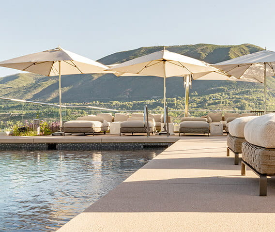 The rooftop pool at the Residences at The Little Nell provides stunning 360 degree panoramic views of Aspen and its surrounding mountains, and plush patio furniture for guests to relax and soak up the sun.